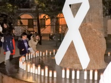 Velas junto a un lazo blanco en recuerdo a las víctimas