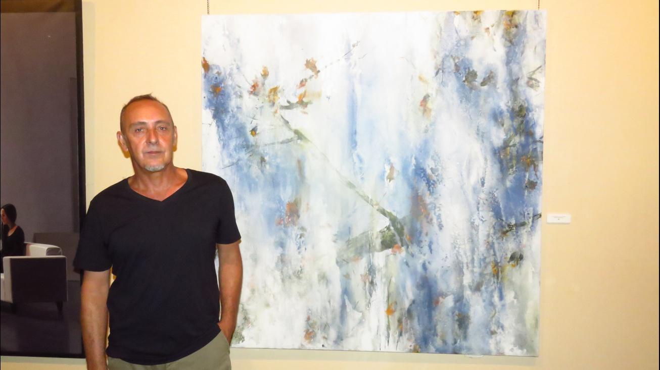 Jesús Mozos junto a una de sus obras en el Certamen de Pintura 2017 de Manzanares